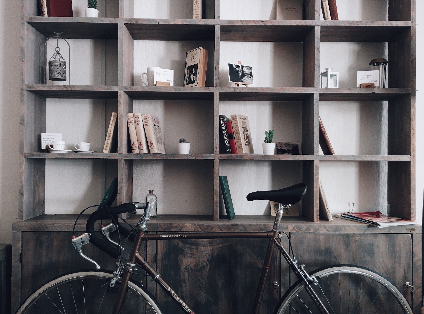 Bicycle in from of wooden book shelf